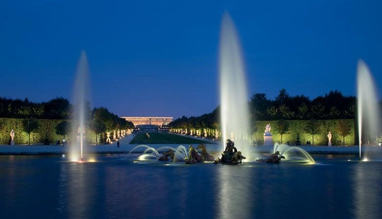 Vista nocturna de las fuentes del castillo de Versalles