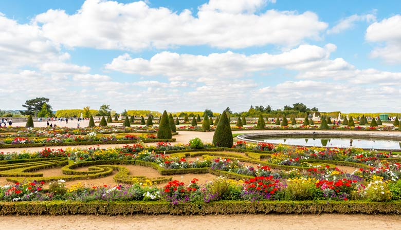 Flowered gardens of Versailles in front of the Palace